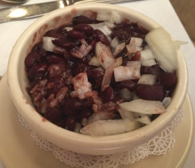 Traditional cuban black bean soup is slow cooked is served with onions and white rice.